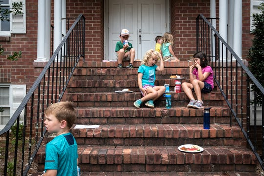 Children sit on the steps of the Travelers Rest United Methodist Church after eating their meals from a food truck Wednesday, July 31, 2019, donated by a group of Riley Fellows from Furman University's Riley Institute.