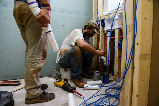 Kevin Poore and Jason Gordon work on plumbing fixtures as construction of Modal, a hostel off of Augusta Road, continues Wednesday, July 31, 2019.