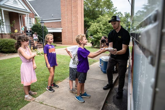 Graham Hall, an intern with Greenville County Schools, help pass out meals to children at Travelers Rest United Methodist Church from a food truck donated by a group of Riley Fellows from Furman University's Riley Institute.