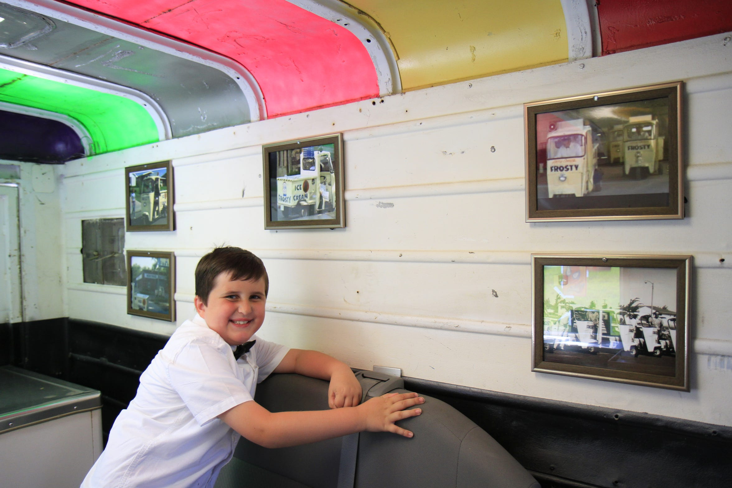 Benjamin Brown posing next to the photos of the original Frosty trucks inside the truck