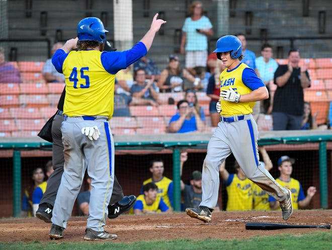 Henderson Flash's Charlie Mooneyham (45) greets teammate Robert Sproul (15) at home plate as both score in the third inning as the Henderson Flash play the Dubois County Bombers at League Stadium in Huntingburg Tuesday, July 30, 2019.