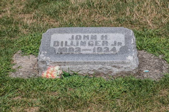 The grave of  John Dillinger Jr., 1909-1934, sits inside the walls of Crown Hill Cemetery in Indianapolis on Tuesday, July 30, 2019. Dillinger's smaller headstone sits in the family plot marked by a larger headstone. Small chunks of the stone, which may have been replaced once, have been chipped off by visitors over the years.
