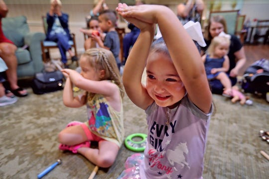 Hailey Jeffries, left, and Riley Palmer join others in dancing to song during Joyful Melodies intergenerational music class at The Hearth at Prestwick in Avon, Monday, July 22, 2019.