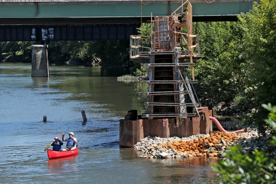 Canoeists maneuver on White River through construction as it continues on the Logan Street bridge in Noblesville, Wednesday, July 31, 2019.  The project has been delayed because of rain and river flooding.  Construction will include widening the bridge and adding a pedestrian walkway with a look-out.