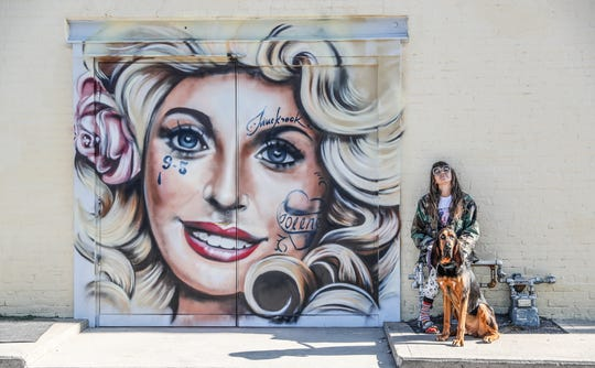 "Jules Muck, also known by her tag Muckrock, and her dog Dada, sit next to one of her latest murals, titled ""Dolly Door"", painted on the side of the Amelia's bakery and Bluebeard building at Norwood Street and Virginia Avenue in Indianapolis, on Wednesday, July 31, 2019."