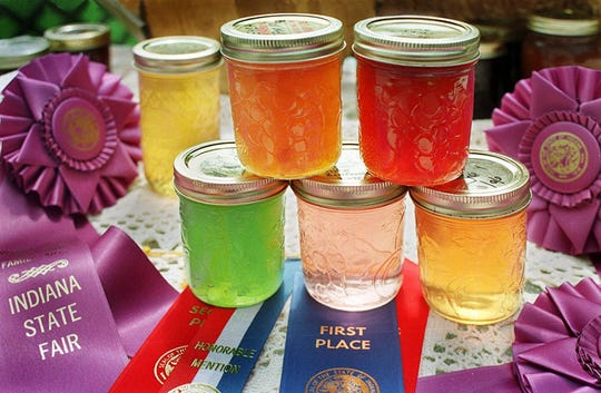 Backlit by the warm late Summer sun, here are six award winning jellies, (left to right) Apple jelly, Mint jelly (green), Peach jam, White Zinfandel (pink) Raspberry jam and corn cob jelly surrounded by many prize ribbons from the State Fair.