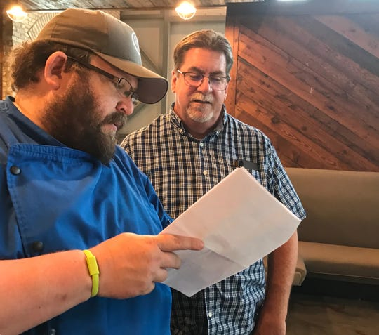 Brent Robinson of Pelahatchie, left, vice president of concept development and franchising for Georgia Blue restaurant group, speaks with Billy Talley of Florence, owner of Teleconnect, about a detail at the new Georgia Blue location in Madison.