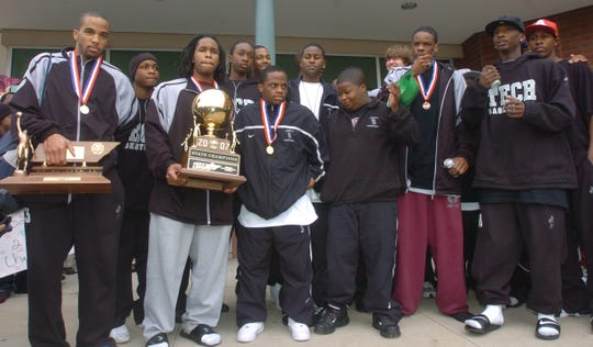 The 2007 Liberty boys basketball team with the Class AA state championship trophy and the Class AA Mr. Basketball trophy, won by Jewuan Long (left), after returning to school with the state title.