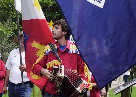 Jacob LeBlanc plays an accordion in a Tintamarre parade during Acadian Culture Day at Vermilionville Sunday, August 13, 2017.