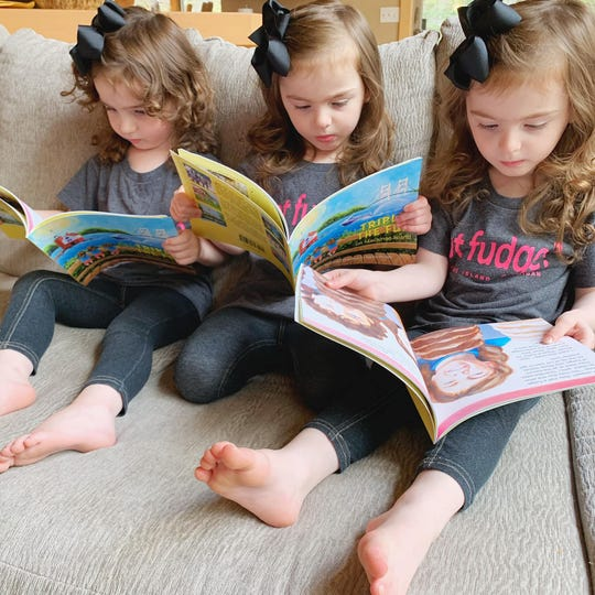 "Triplets Ellie, Josie and Rosie read a new book their mother Victoria Buursma, a Howell native, wrote about the 3-year-old sisters and their adventures on Mackinac Island, ""Triple the Fun on Mackinac Island."""