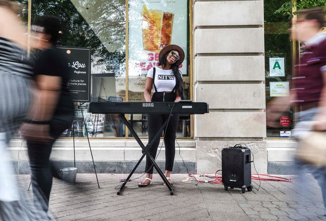 Chanson Calhoun performs and sings for two hours Wednesday as part of a Louisville Tourism and Fund for the Arts as part of a new street performers program near Fourth Street Live. July 31, 2019