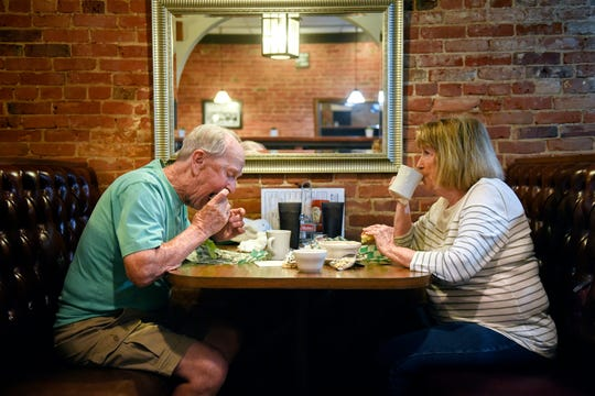 Duane Chadwell, left, and his wife Connie enjoy olive burgers at Weston's Kewpee Burger on Tuesday, July 16, 2019, in Lansing.