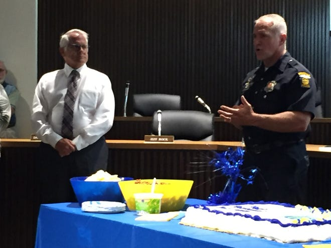 Mansfield police Detective Rich Miller addresses the crowd at his retirement reception on Wednesday as Mayor Tim Theaker looks on.