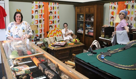 The Marion County Historical Society will celebrate its 50th anniversary with an open house from 1-4 p.m. Saturday. Director Brandi Wilson, left, stands in the exhibit of a 1960s-style family room that is on display at the historical society.