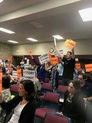 "Wauwatosa residents hold up orange ""agree"" and ""disagree"" signs in protest during the July 30 community affairs committee meeting in Wauwatosa City Hall. Many opposed changing the zoning for Midtown Tosa to allow for more than three stories on developments."