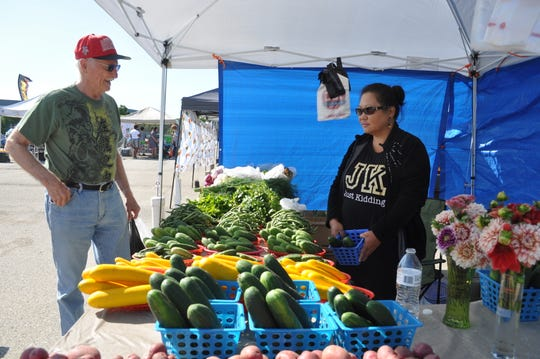 Floyd Woldt browses vegetables being sold by Vivian Ly at the Brown Deer Farmers Market on July 31.