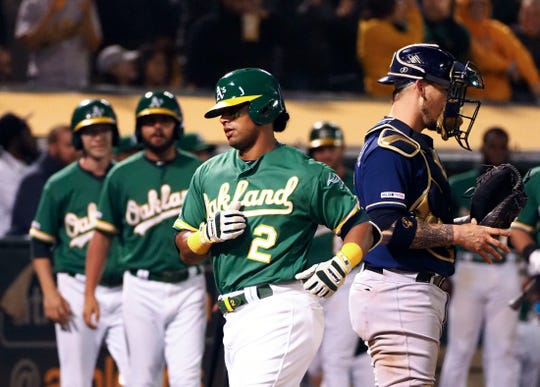 Athletics designated hitter Khris Davis crosses home plate after his solo home run in the eighth inning.