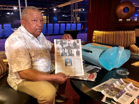 Lebronze Davis shows a reporter newspaper articles about him and his brothers during a reunion at a hotel-casino on Friday, July 12, 2019 in Tunica, Miss.
