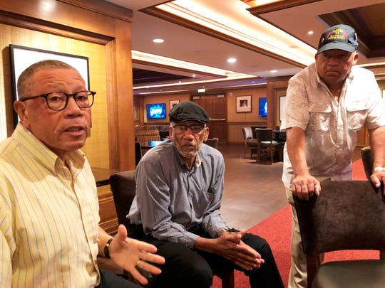 In a Friday, July 12, 2019 photo, Arguster Davis, left, and his brothers Nathaniel, center, and Lebronze talk with a reporter during a reunion at a hotel-casino, in Tunica, Miss.