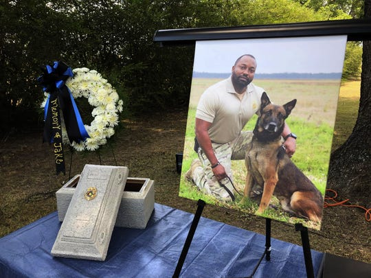 A Tuesday, July 30, 2019 photo shows Alabama K-9 Jake, who died after coming into contact with a narcotic during a prison contraband search, was honored Tuesday with a 21-gun salute and commendation from Gov. Kay Ivey at the Staton Kennel Complex in Elmore. Pictured in the portrait is Jakes handler Sgt. Quinton Jones.