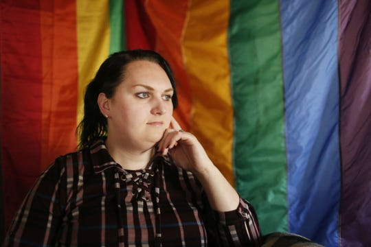 Destiny Clark, 33, of Odenville, Ala., sits in front of a pride flag for a portrait in Odenville, Ala. Three transgender persons including Clark have filed a lawsuit challenging Alabama's requirement for a person to show proof of sex-altering surgery in order to change the gender designation on their driver's license.