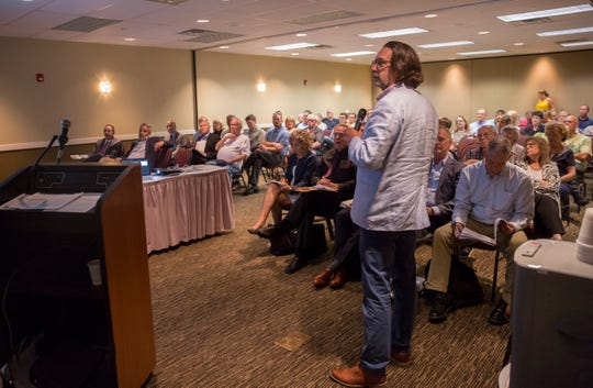 Officials present the project plans for a downtown apartment complex along the White River Tuesday night at the Horizon Convention Center. The developer of the project will go before city council on Aug. 5 for final economic agreement approvals.