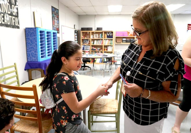 Stephanie Caballero-Cisnero, left, shakes hands with third-grade teacher Barbara Arnold, right during the Hobgood Elementary open house on Tuesday, July 30, 2019, before the start of the 2019-20 school year.