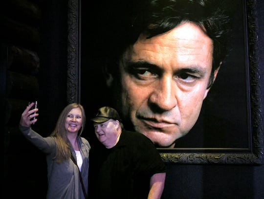 Josie Bisto and Ted Sidelinger take a selfie together against a large photograph of Johnny Cash inside Johnny Cash's Kitchen and Saloon on Wednesday, July 31, 2019.