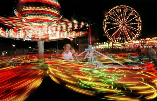 As the Ferris wheel lights up the night sky, a couple of visitors enjoy the Sizzler ride at the Wilson County Fair on Aug. 16, 1998.