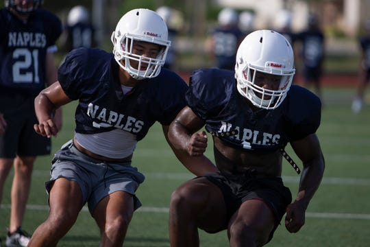 Naples High School's Devin Moore, left, and AJ Powell run through defensive drills during practice, Wednesday, July 31, 2019, at Naples High School.