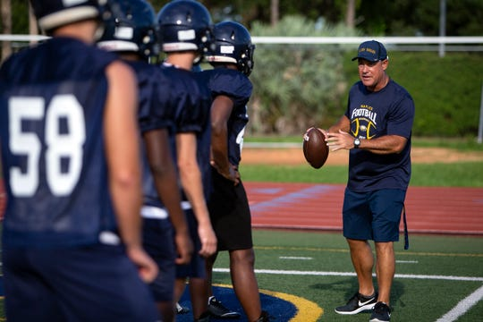 Naples High School defensive coordinator Mike Sawchuk works with his team, Wednesday, July 31, 2019, at Naples High School.