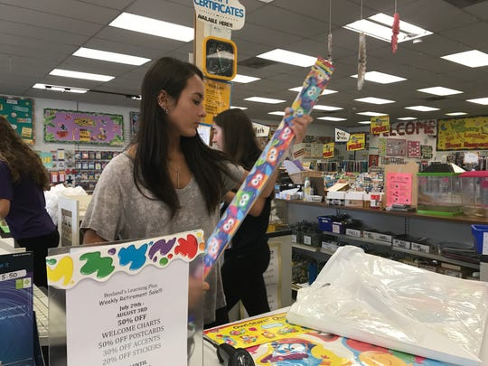 Alexis Van Benschoten helps ring up a customer at Bosland's Learning Plus, helps ring up a customer at the teacher supply store.