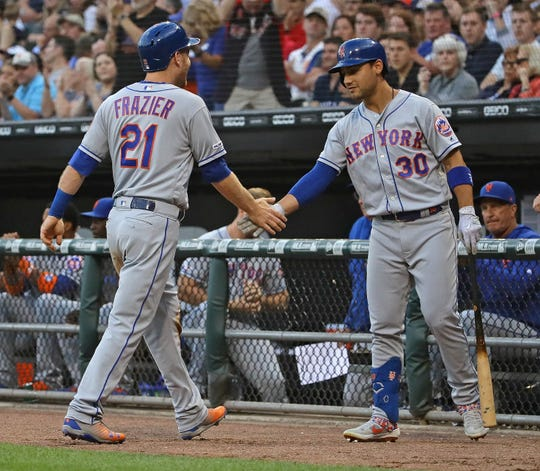 Todd Frazier #21 of the New York Mets is congratulated by Michael Conforto #30 after scoring a run in the 2nd inning against the Chicago White Sox at Guaranteed Rate Field on July 30, 2019 in Chicago, Illinois.