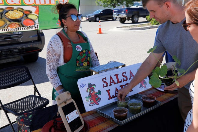 Farmington vendor Flor Rodriguez has visitors taste her salsa during the opening day of the annual Farmington Growers Market in June. The market returns each Saturday and Tuesday to the parking lot at the Farmington Museum at Gateway Park.