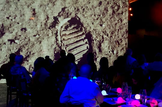 Guests watch a video of the first moon walk at PS Underground on Saturday, July 20, 2019.