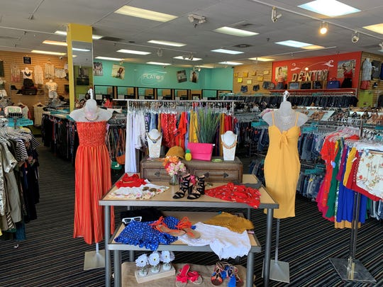 Front display table with vibrant summer styles at the entry to Plato's Closet in Palm Desert.