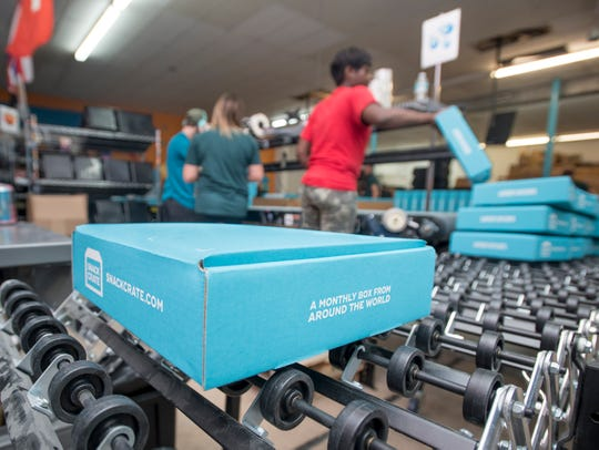 Workers fill boxes along an assembly line at Snack Crate in downtown Pensacola on Wednesday, July 31, 2019.