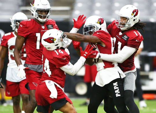 Arizona Cardinals' Larry Fitzgerald (right) jumps in to stop a dust-up between Damiere Byrd (14) and Robert Alford (23) during training camp on July 30, 2019 in Glendale, Ariz.