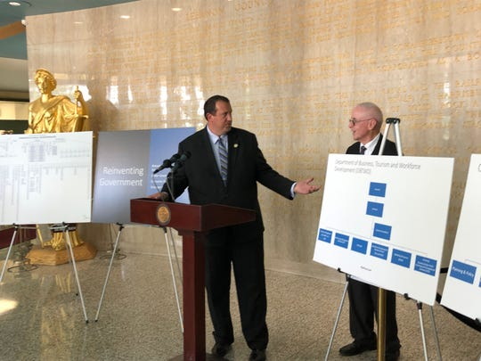 State Rep. Seth Grove of York County, left, stands with state Rep. Frank Ryan of Lebanon County between flow charts that help explain their proposal to streamline Pennsylvania's government.