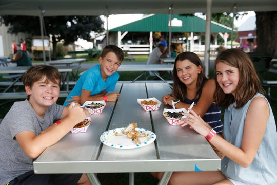 From left, Charlie Huntington, Rifi & Nina Rogers and Scarlett Huntington enjoy fair food at the Ulster County Fair in New Paltz on July 31, 2019.