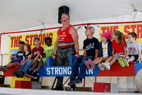 "John ""The Strong Man"" Beatty of Tolono, lifts eight children on a platform during his show at the Ulster County Fair in New Paltz on July 31, 2019.  The combination of children weighed over 700 pounds."