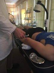 Ben Bills is shown here receiving an acupuncture treatment that helped him overcome a major elbow issue.