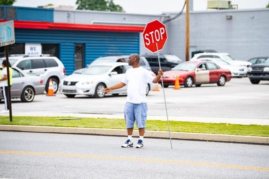 Fred Walker makes sure to stop traffic so cars waiting across the street from the gas station can get their free gas. The giveaway proceeded Wednesday in an orderly manner.