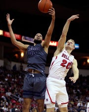 Nevada's Caleb Martin , left, pulls in a rebound over Fresno State's Sam Bittner   on Jan. 12, 2019.