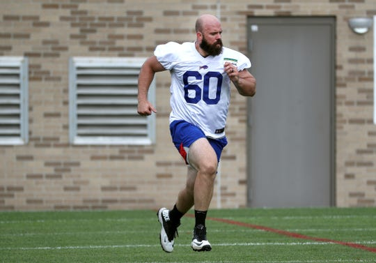 Bills center Mitch Morse works with a trainer on the side after being diagnosed with a concussion.
