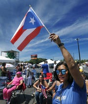 Gladys Pedraza-Burgos of Rochester waves a Puerto Rican flag during the 48th Annual Puerto Rican festival at the Frontier Field VIP Parking Lot.