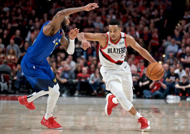 FILE - In this May 3, 2019, file photo, Portland Trail Blazers guard CJ McCollum, right, dribbles past Denver Nuggets guard Will Barton. McCollum has agreed to a three-year contract extension with the Trail Blazers.