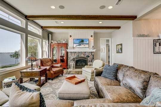 The living room features a gas fireplace with a cut-stone surround as well as North Carolina hand-sewn beam accents spanning the 10-foot ceilings.