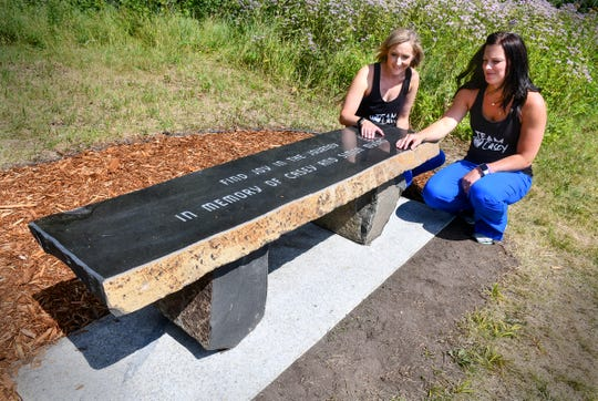 Ashley Fogarty and Cassie Sandstrom reflect near a bench dedicated to Casey and Simon Myers near a walking trail Wednesday, July 31, 2019, at the CentraCare Plaza in St. Cloud. Casey and Simon Myers were killed in a vehicle crash in December, 2018.