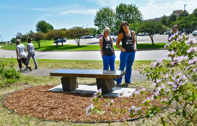 Ashley Fogarty and Cassie Sandstrom view a granite bench recently dedicated to Casey and Simon Myers near a walking trail Wednesday, July 31, 2019, at the CentraCare Plaza in St. Cloud.
